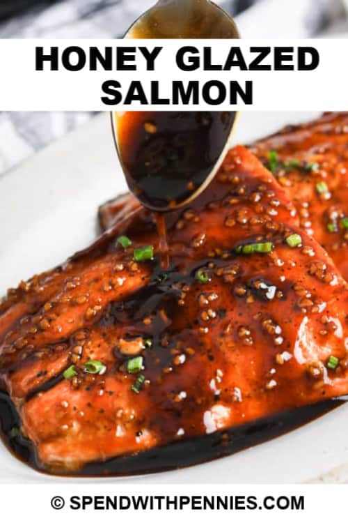 Sauce poured over two honey glazed salmon filets with chives with writing.