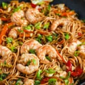 A pan of shrimp lo mein with vegetables and noodles garnished with green onions