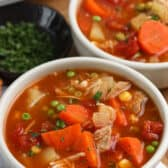 Slow Cooker Turkey Vegetable Soup in a white bowl with garnish