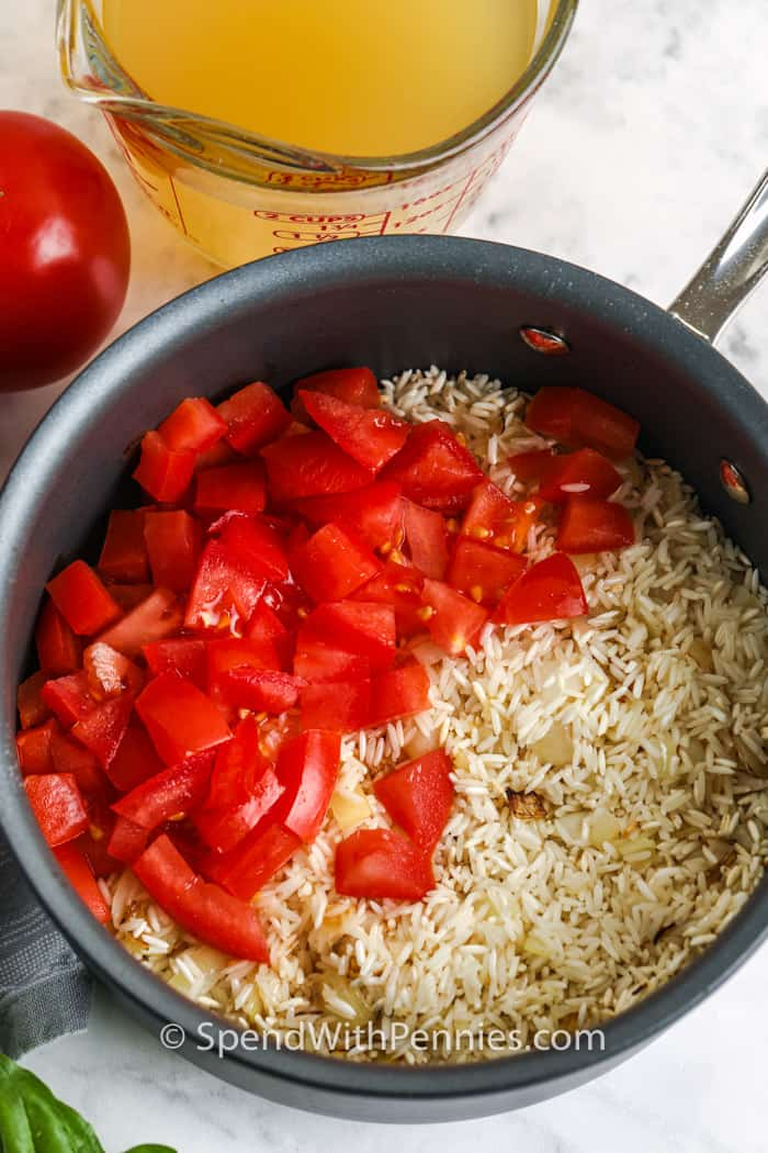 Tomato Basil Rice ingredients in a pot with broth on the side
