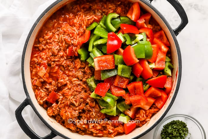 green and red bell peppers on top of sausage cooked with rice in tomato sauce