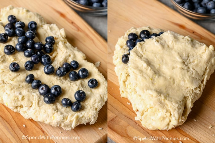 Blueberry Scone dough on a wooden board with blueberries being folded in