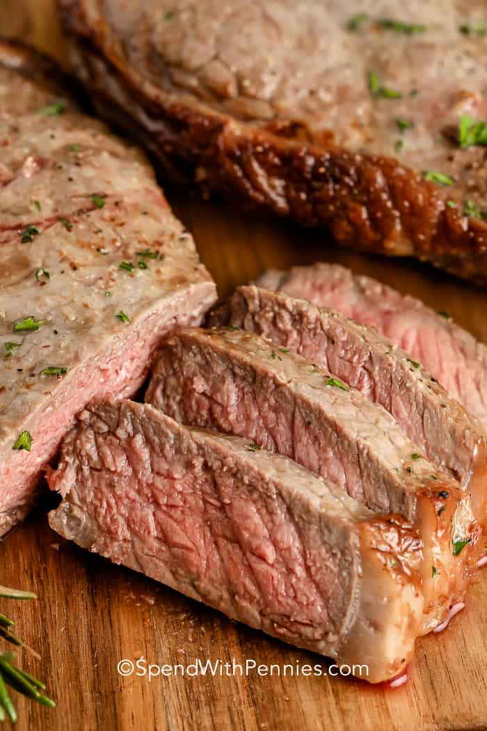 Air Fryer Steak cut into slices on a wooden board