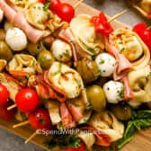 antipasto skewers on a wooden board with basil as garnish