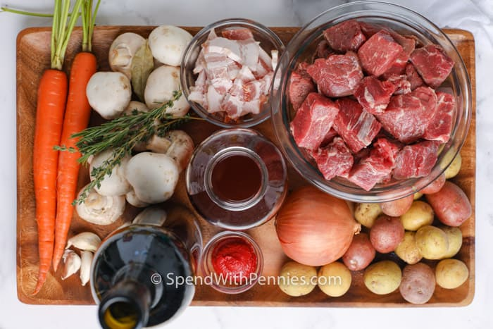 ingredients to make Beef Bourguignon on a wooden board