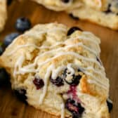a blueberry scone with drizzle on a wood cutting board