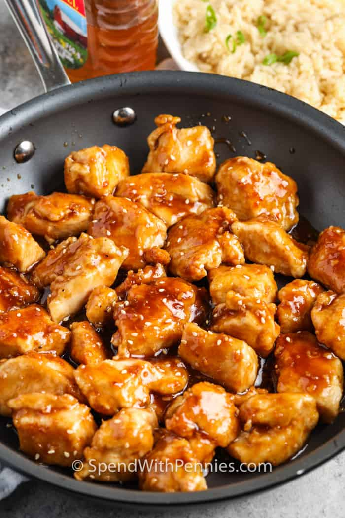 Honey Chicken in a pan with rice in the back