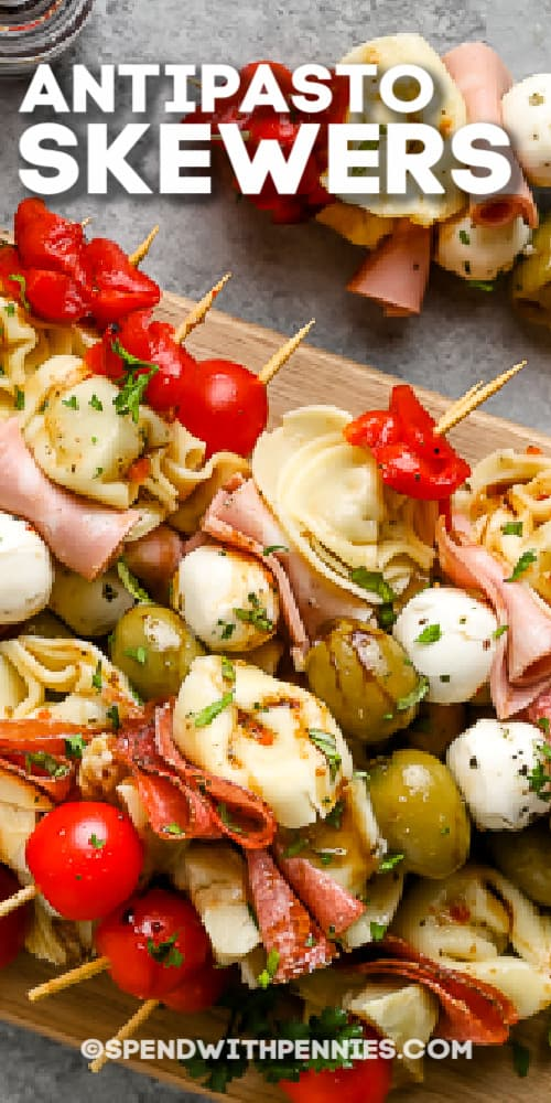 antipasto skewers on a wooden board with writing