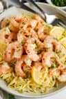 Shrimp Scampi in a bowl with lemon slices and fork