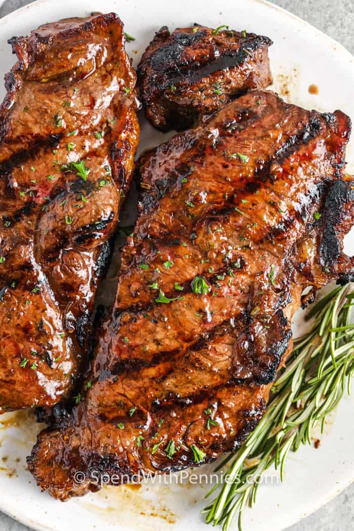 2 steaks on a plate with rosemary for Steak Marinade