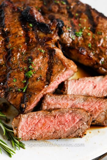 slices of steak on a plate with herbs and Steak Marinade