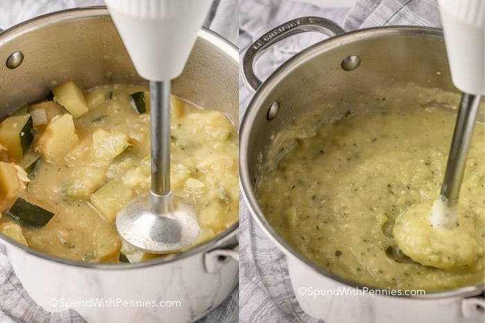 blending zucchini soup in a silver pot with a hand blender