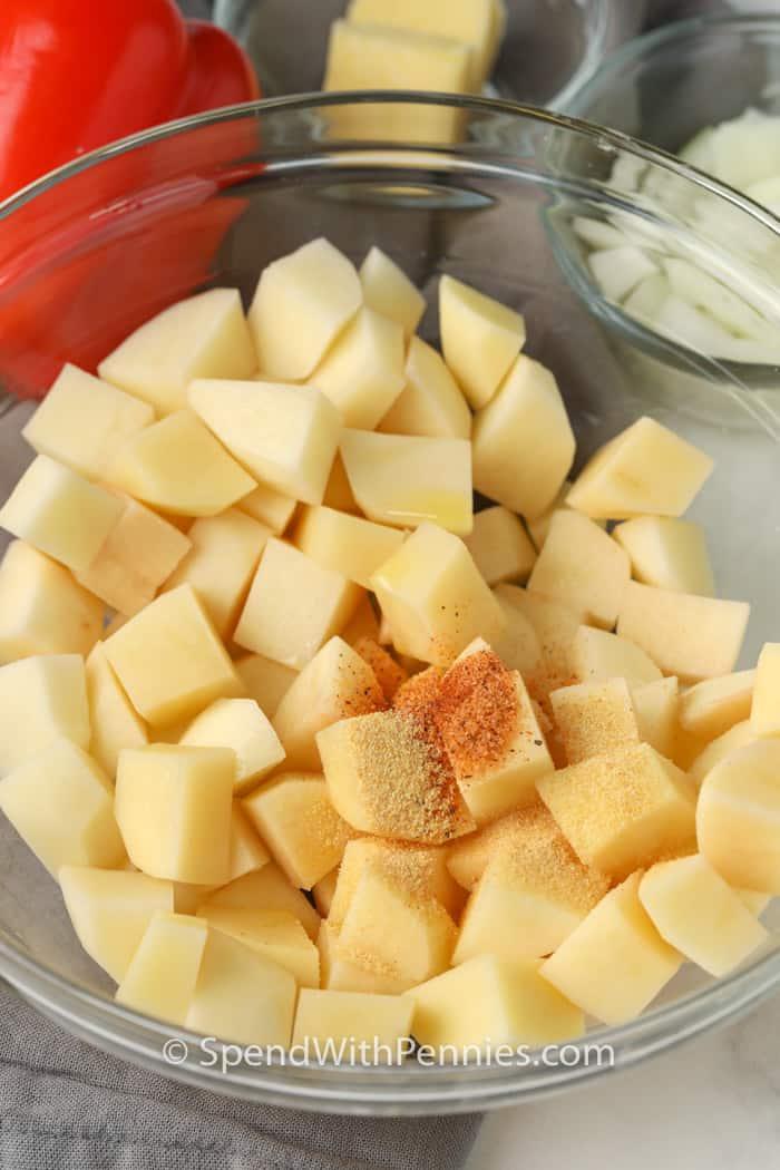 adding seasoning to potatoes to make Air Fryer Home Fries