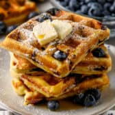 stack of Blueberry Waffles on a plate with syrup and squares of butter