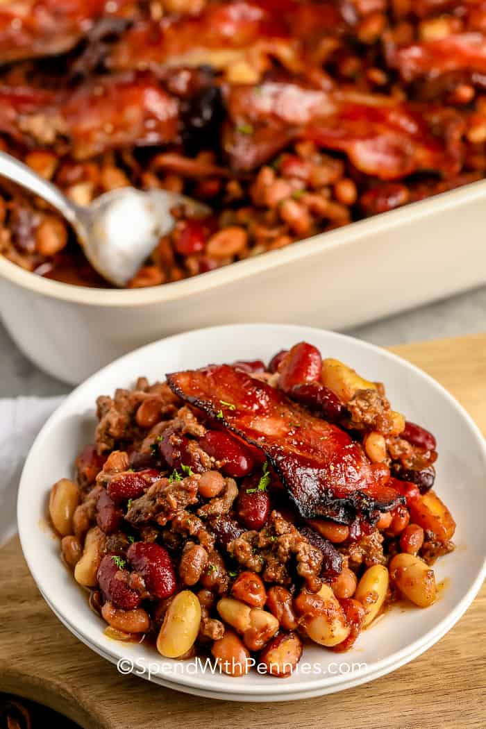 Cowboy Baked Beans on a plate with the casserole dish in the background