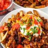 plate full of Chili Cheese Fries with a bowl of tomatoes in the back