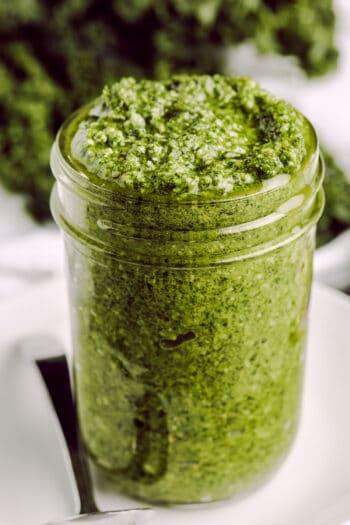 close up of Kale Pesto in a mason jar with a spoon and kale in the background