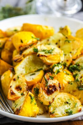 close up of cooked Roasted Patty Pan Squash with Herb Oil on a white plate with a fork and garnished