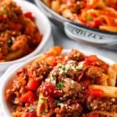 Sausage Pasta in a bowl with pan and bowl full in the background
