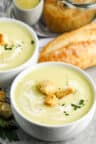 close up of a bowl of Turnip Soup with bread and pot in the background