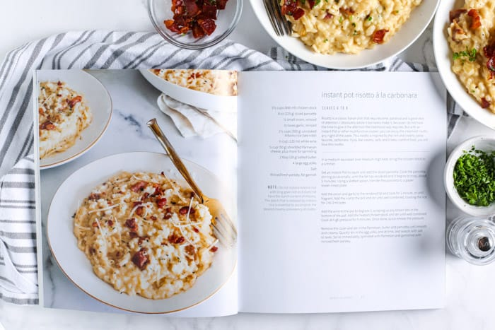 an open cookbook next to bowls of risotto