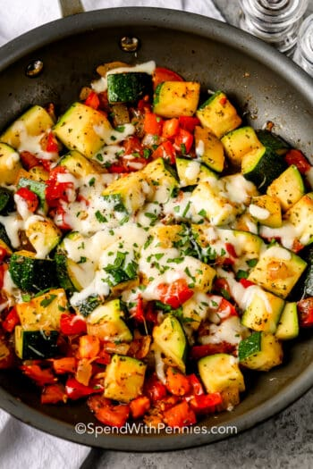 Sauteed Zucchini in a frying pan topped with cheese