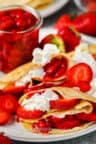 Strawberry Crepes on a plate with jar of strawberries in the background