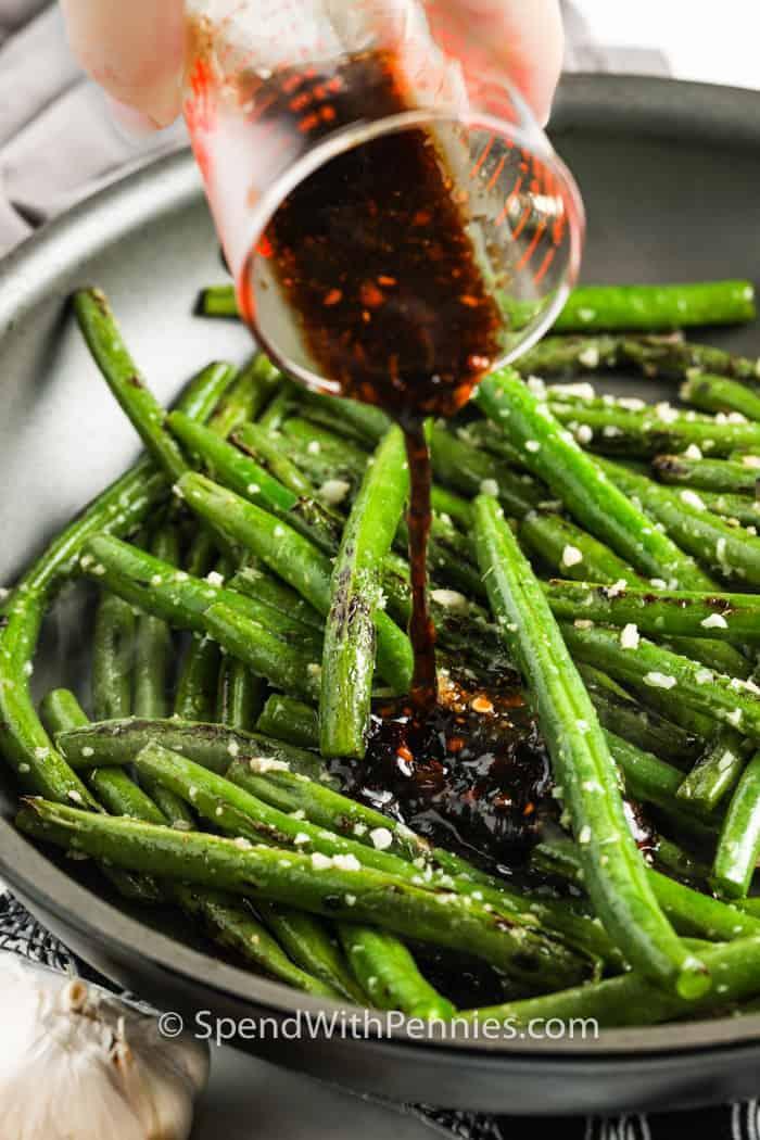 pouring sauce on Szechuan Green Beans