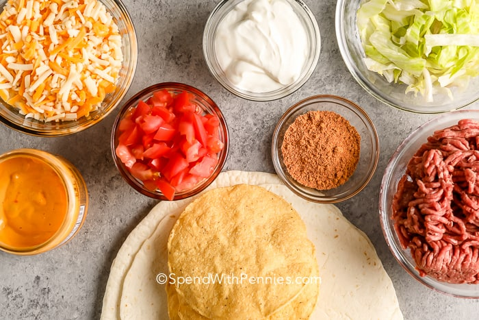 ingredients for copycat Crunchwrap Supreme on a marble board