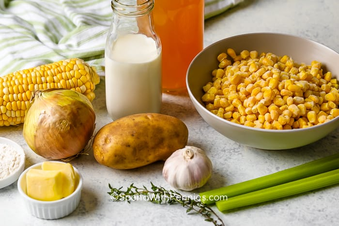 Corn kernel in a bowl with a corn on the cob, an onion, a potato, clove of garlic, jar of cream, side of butter, celery stalks, tablespoon of flour, and chives
