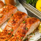 close up of Salmon Seasoning on cooked salmon with lemon and garnish in the back