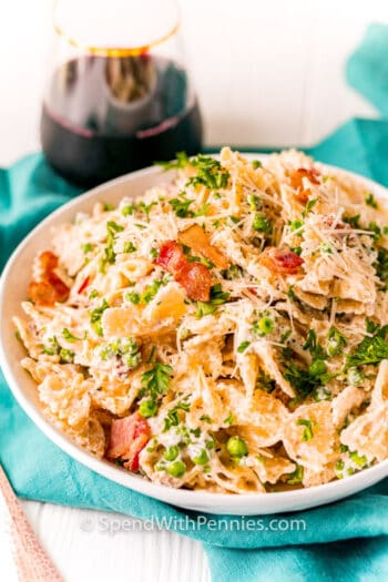 Farfalle with Bacon in a bowl with a glass of wine in the back