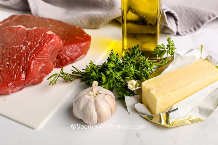 Uncooked steak on a cutting board with garlic, butter and rosemary