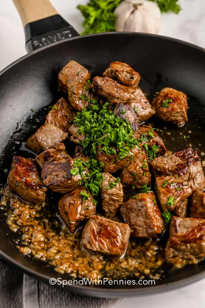 Steak bites in garlic butter, garnished with parsley in a pan