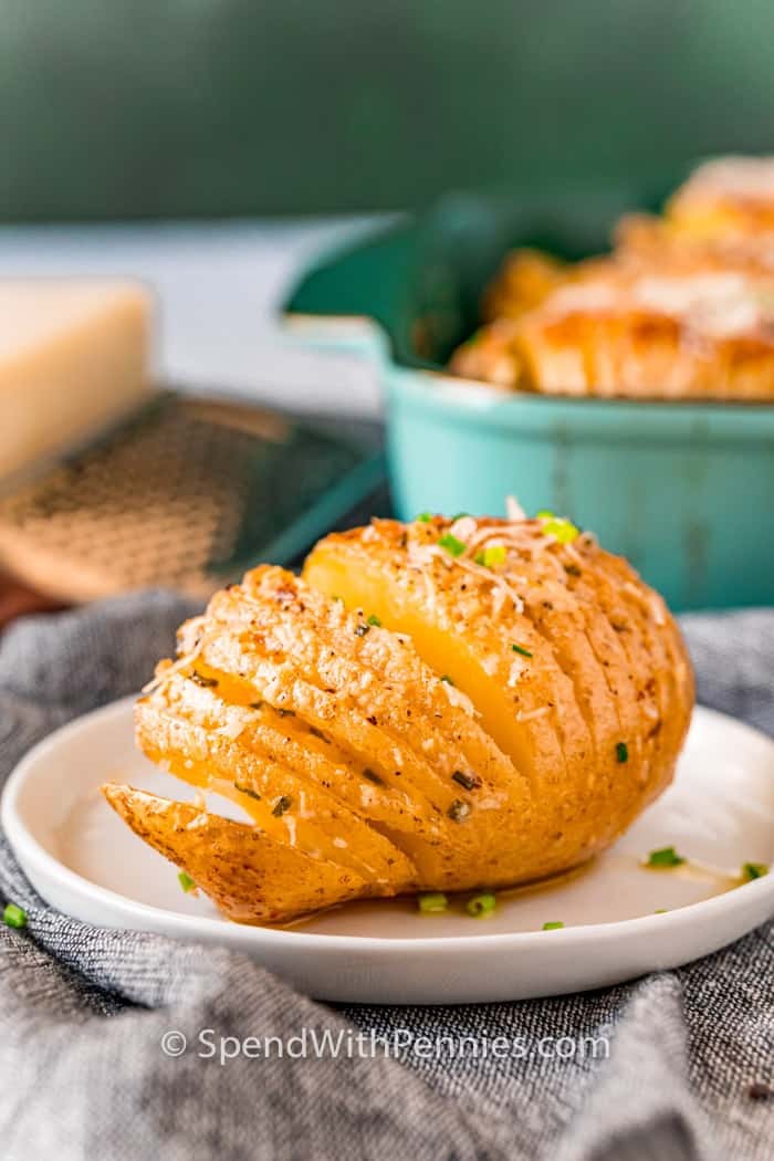Hasselback Potatoes in a casserole dish with one plated potatoe sliced