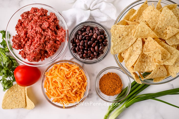 A bowl of uncooked ground beef, a bowl of black beans, a bowl of shredded cheese, a bowl of tortilla chips and a bowl of spices