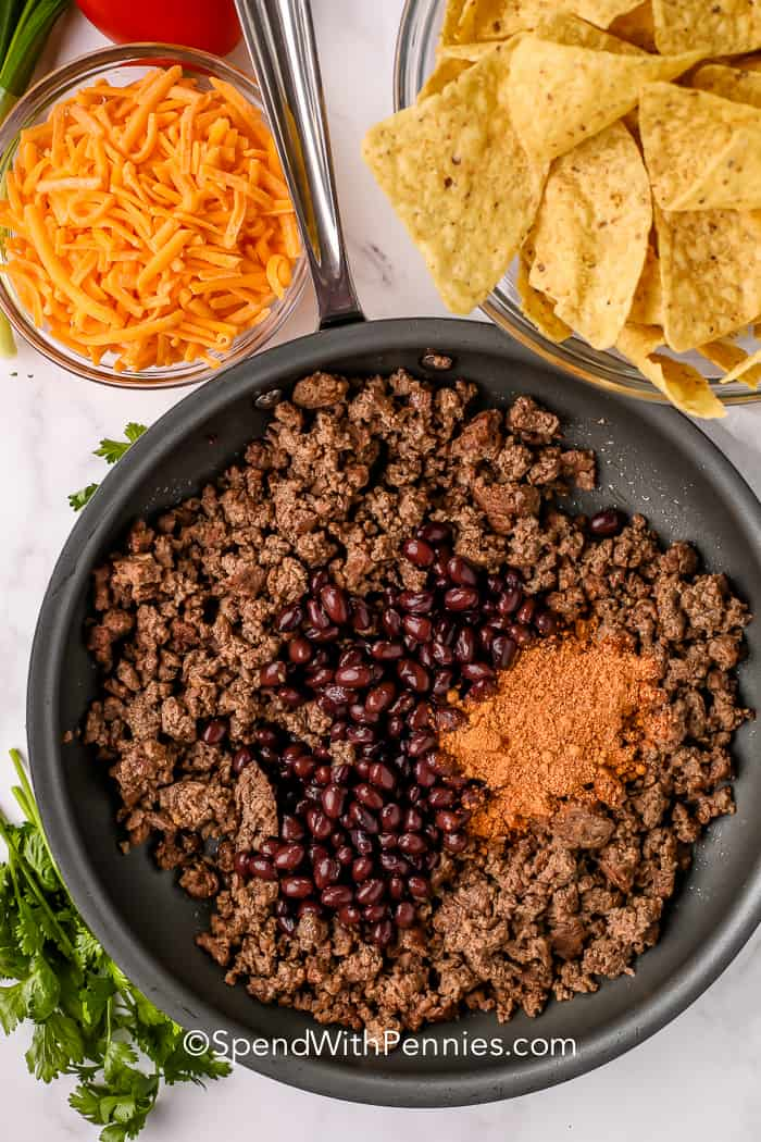 A pan with cooked ground beef, black beans and seasoning, a bowl of shredded cheese, and a bowl of tortilla chips