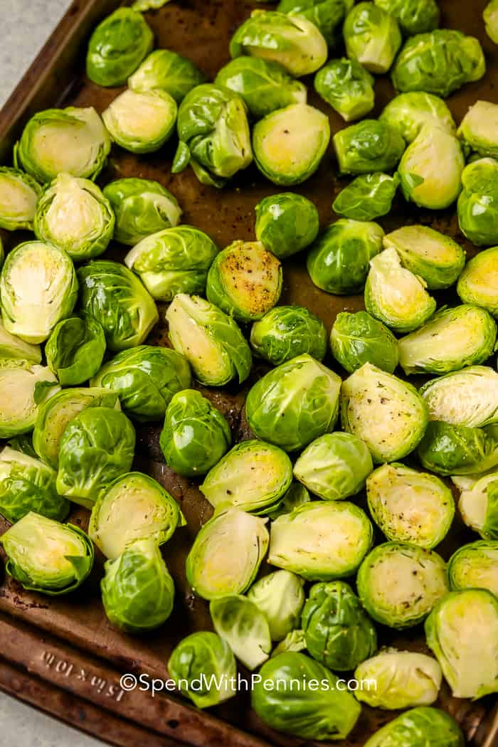 Uncooked, halved brussel sprouts, oiled and seasoned with pepper in a baking tray