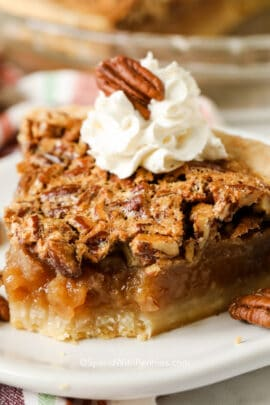 A slice of pecan pie with whipped cream and pecans