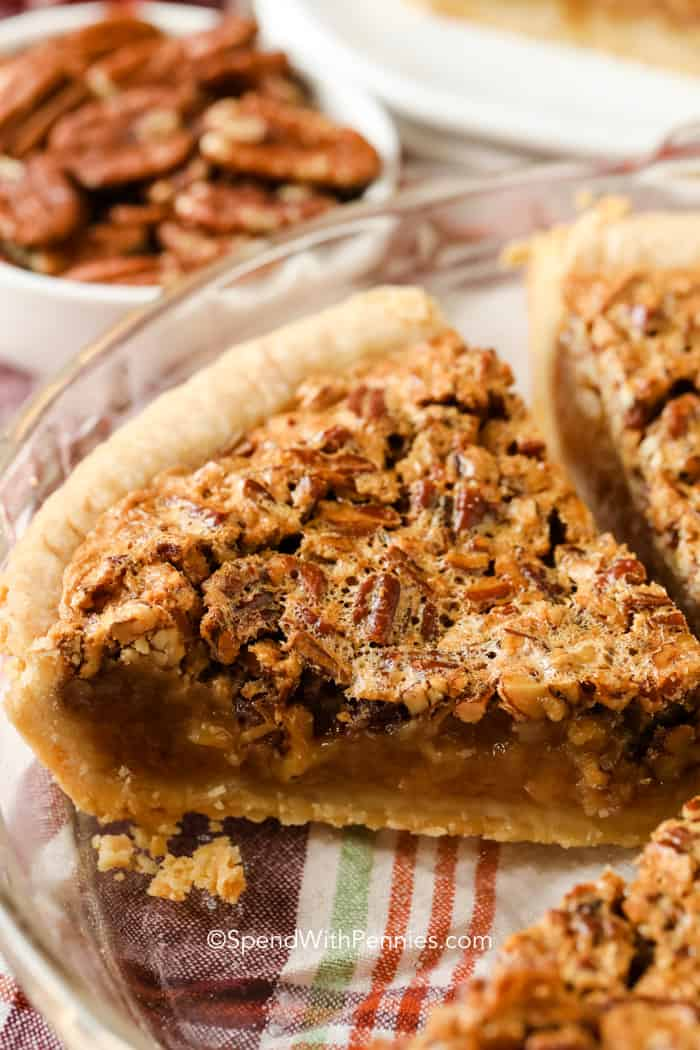 A slice of pecan pie in a pie plate