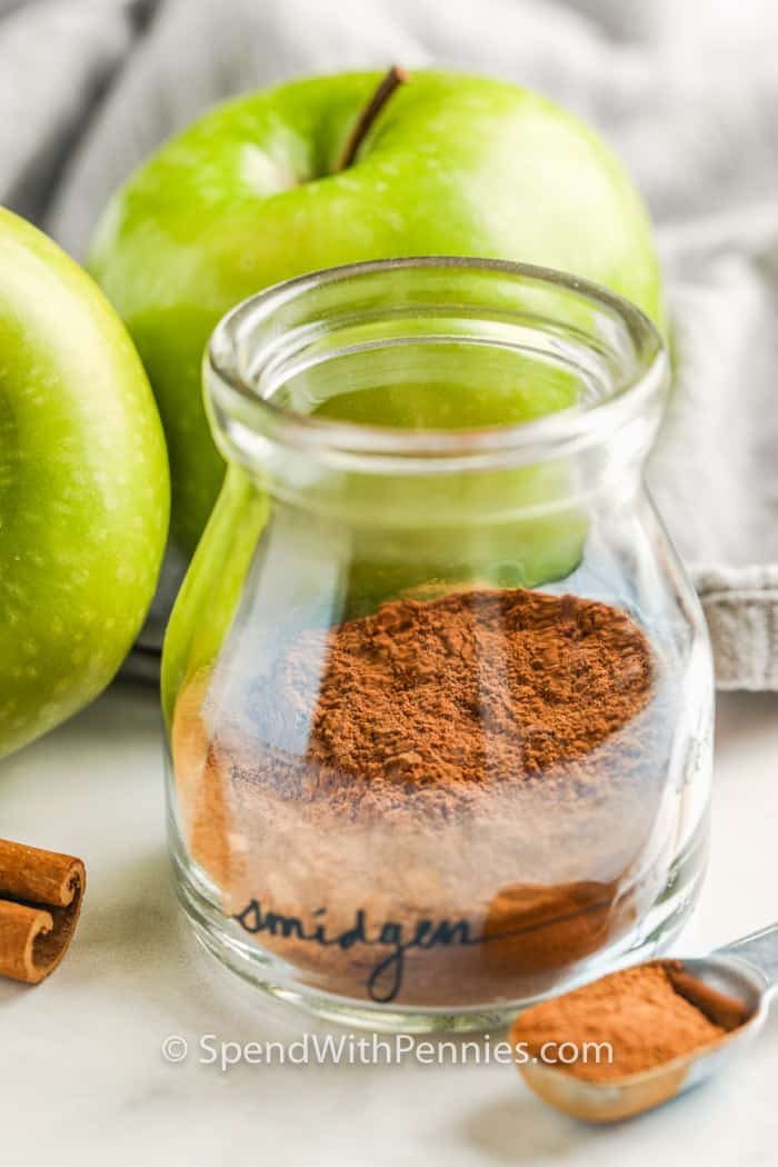 Apple Pie Spice in a jar with apples and cinnamon beside it