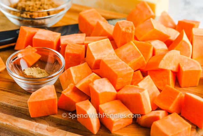 close up of cut up sweet potatoes on a cutting board to make Brown Sugar Roasted Sweet Potatoes