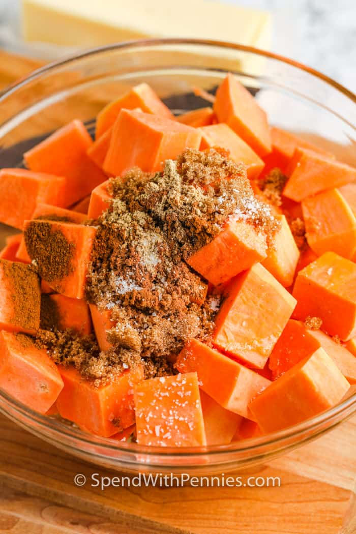 adding sugar and spices to potatoes to make Brown Sugar Roasted Sweet Potatoes