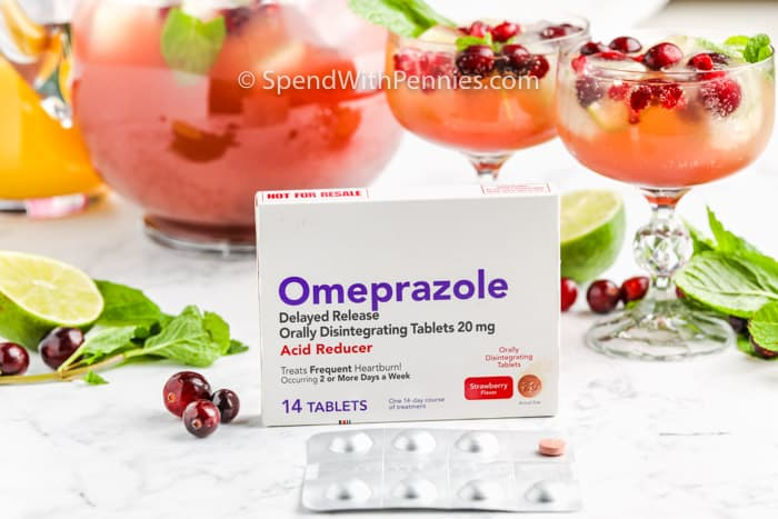 Champagne Punch with glasses and a pack of Omeprazole in the foreground