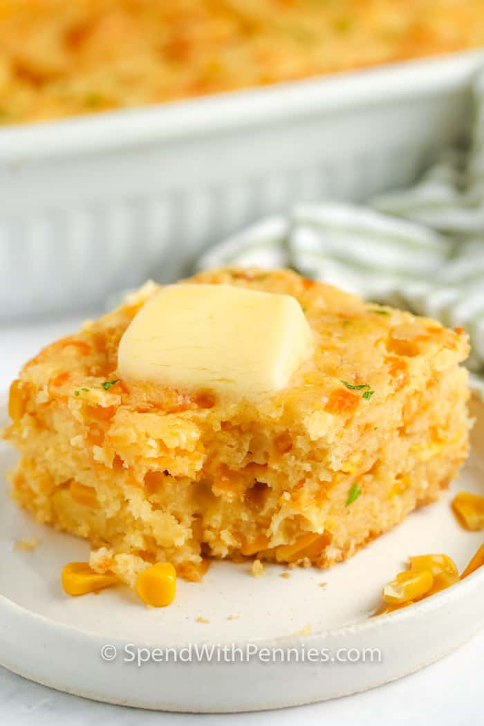 Cornbread Casserole on a dish with butter and a bite taken out
