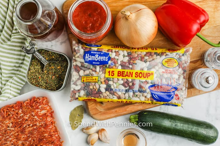 Crock Pot Italian Bean Soup ingredients on a cutting board and table