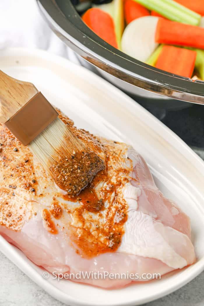 brushing sauce on turkey to make Crockpot Turkey Breast