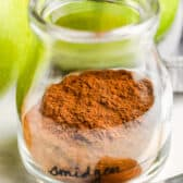 close up of Apple Pie Spice in a glass jar with apples in the back