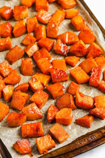 cooked Brown Sugar Roasted Sweet Potatoes on parchment paper and baking sheet