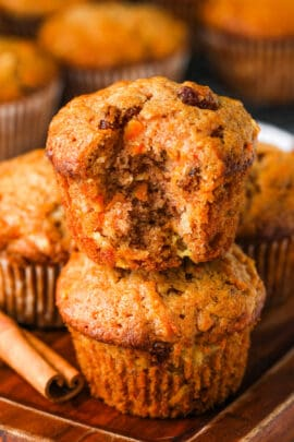 two Carrot Muffins stacked with one muffin with a bite taken out and a cinammon stick